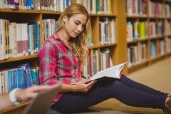 Skoncentrowany żeński uczeń pracuje na podłoga zdjęcia royalty free