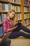 Skoncentrowany żeński uczeń pracuje na podłoga fotografia royalty free