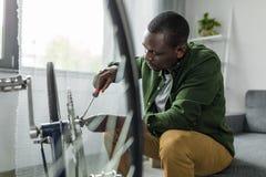 skoncentrowany afro mężczyzna naprawiania bicykl z śrubokrętem obraz stock
