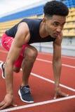 Skoncentrowany afrykański atleta mężczyzna przygotowywający zaczynać zdjęcie stock