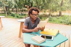 Skoncentrowany afrykański młodego człowieka obsiadanie i czytelnicza książka obraz stock