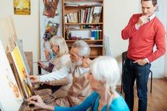 Skoncentrowany artysta kontroluje jego kolegów w obraz klasie obrazy stock