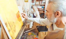 Skoncentrowany artysta maluje obrazek w klasie zdjęcia royalty free