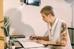 Skoncentrowany artysta niesie barwionego ołówek z rękami zakrywać w tatuażach zdjęcie royalty free