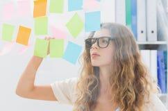Skoncentrowany artysta patrzeje kolorowe kleiste notatki zdjęcia royalty free