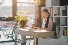 Skoncentrowany atrakcyjny azjatykci bizneswoman pracuje z laptopem przy miejscem pracy w biurze obraz royalty free