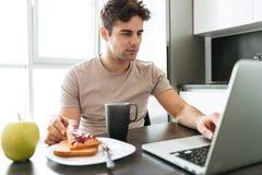 Skoncentrowany atrakcyjny mężczyzna używa laptop podczas gdy jedzący śniadanie obrazy royalty free