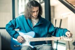 Skoncentrowany atrakcyjny niezwykły faceta utworzenie zawiązuje na jego elektronicznej gitarze zdjęcie stock
