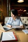 Skoncentrowany Azjatycki doradca analizuje mapę w kawiarni zdjęcie stock