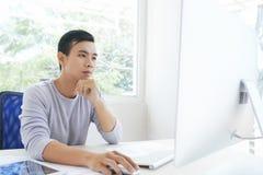 Skoncentrowany Azjatycki projektant przy pracą zdjęcia stock