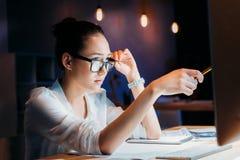 Skoncentrowany azjatykci bizneswoman wskazuje przy komputerowym monitorem w eyeglasses Zdjęcia Royalty Free