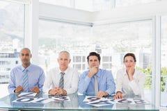 Skoncentrowany biznes drużyny obsiadanie z ich głosowaniem na biurku zdjęcie royalty free