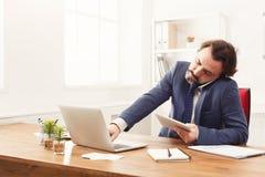 Skoncentrowany biznesmen opowiada na telefonie komórkowym zdjęcie stock