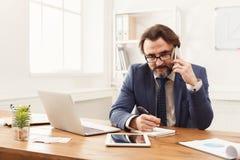 Skoncentrowany biznesmen opowiada na telefonie komórkowym zdjęcia royalty free