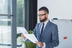 Skoncentrowany biznesmen patrzeje dokumenty w rękach w biurze zdjęcie royalty free