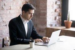 Skoncentrowany biznesmen patrzeje laptop i pisać na maszynie fotografia royalty free