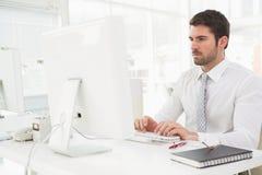 Skoncentrowany biznesmen pisać na maszynie na klawiaturze obrazy royalty free
