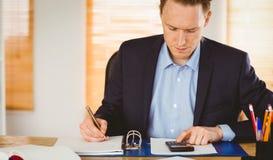 Skoncentrowany biznesmen pisze puszku obrazy stock