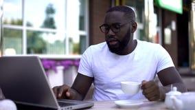 Skoncentrowany biznesmen pracuje na laptopie i trzyma filiżankę w kawiarni, ruchliwie obraz stock