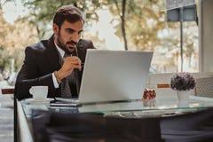 Skoncentrowany biznesmen pracuje na laptopie i trzyma sunglas fotografia stock