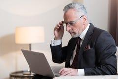 Skoncentrowany biznesmen pracuje z laptopem w hotelu zdjęcia stock