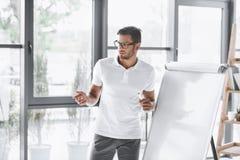 skoncentrowany biznesmen robi prezentaci przy białą deską obraz royalty free