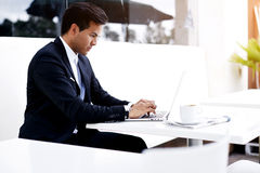 Skoncentrowany biznesmen w eleganckim kostiumu keyboarding tekscie na jego laptopie podczas gdy siedzący na restauracja tarasie p Zdjęcie Royalty Free