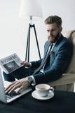 Skoncentrowany biznesmen w karle pracuje na laptopie zdjęcia royalty free
