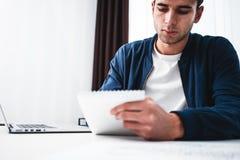 Skoncentrowany biznesmena chwyta notepad podczas gdy siedzący biurkiem przy ofiice zdjęcia stock