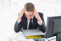 Skoncentrowany biznesmena czytania dokument przy biurowym biurkiem obraz royalty free