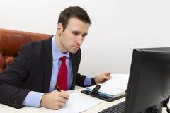 Skoncentrowany biznesowy mężczyzna wypełnia papierowego dokument fotografia stock