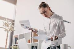 Skoncentrowany bizneswoman czyta biznesowych dokumenty w biurze Zdjęcie Stock