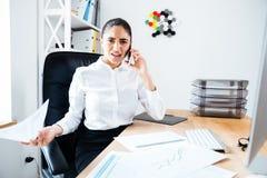 Skoncentrowany bizneswoman opowiada na telefonie podczas gdy siedzący przy miejscem pracy zdjęcia stock