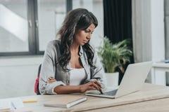 Skoncentrowany bizneswoman pisać na maszynie na laptopie przy miejscem pracy w biurze obrazy royalty free