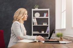 Skoncentrowany bizneswoman pracuje na laptopie przy biurem zdjęcie royalty free