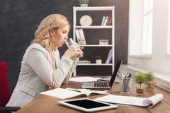 Skoncentrowany bizneswoman pracuje na laptopie przy biurem zdjęcia royalty free