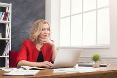 Skoncentrowany bizneswoman pracuje na laptopie przy biurem fotografia royalty free