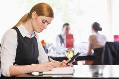 Skoncentrowany bizneswomanu mienia telefon podczas gdy pisać obrazy royalty free