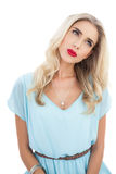 Skoncentrowany blondynka model w błękit sukni patrzeje daleko od zdjęcia royalty free