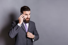 Skoncentrowany brodaty biznesmen opowiada na telefonie zdjęcie royalty free