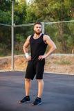 Skoncentrowany brodaty mężczyzna w sportswear pozyci z rękami na biodrach obrazy royalty free