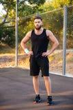 Skoncentrowany brodaty mężczyzna w sportswear pozyci z rękami na biodrach obrazy stock