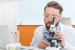 Skoncentrowany brodaty naukowiec pracuje z mikroskopem obraz royalty free