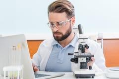 Skoncentrowany brodaty naukowiec pracuje z mikroskopem i laptopem obrazy stock