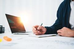 Skoncentrowany budynku projektant pracuje z rysunku competer i planem podczas gdy siedzący stołem przy pracownianym biurem fotografia stock