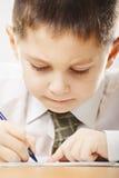 Skoncentrowany caucasian chłopiec writing zbliżenie obrazy stock