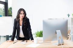 skoncentrowany ciężarny bizneswoman patrzeje komputer zdjęcia stock