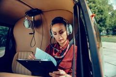 Skoncentrowany ciemnowłosy bizneswoman podrzuca przez dokumentów podczas gdy będący ubranym hełmofon zdjęcia royalty free