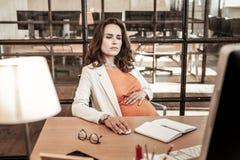 Skoncentrowany ciemnowłosy kobiety obsiadanie w biurowym karle i działaniu zdjęcie stock