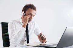 Skoncentrowany czarny biznesmen na telefonie fotografia royalty free